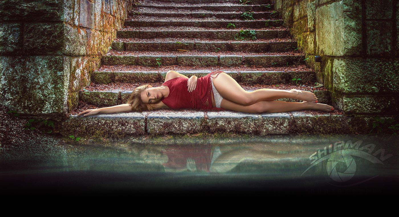 Young woman lying on steps beside a reflecting pool