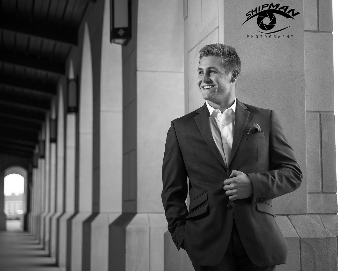 Smiling senior portrait of a boy in downtown Tulsa looking cool