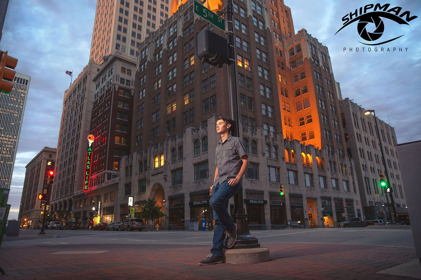 a young man's senior portrait on a street corner in downtown Tulsa