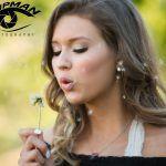 natural light senior portrait of a girl blowing a dandelion