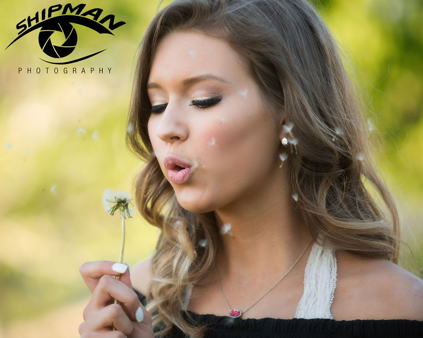 natural light senior portrait of a girl blowing a dandelion